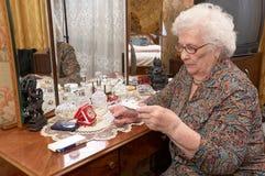Senior woman takes out pills Stock Image