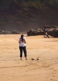 Senior woman takes photo on beach stock image