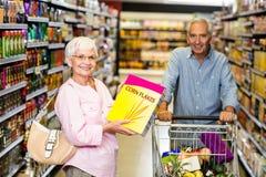 Senior woman taking a box corn flakes Royalty Free Stock Photos