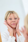 Senior woman taking care of her face skin Stock Photos