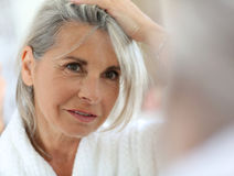 Senior woman taking care of skin in bathroom Royalty Free Stock Photos