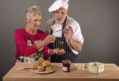 Senior woman taking cooking lessons with chef. Senior women taking cooking lessons with mature chef stock image