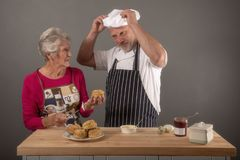 Senior woman taking cooking lessons with mature chef royalty free stock images