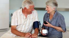 Senior woman taking her husbands blood pressure Stock Image