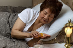 Senior woman taking her medicine at nighttime due to sickness Royalty Free Stock Photography