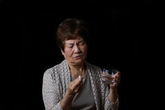 Senior woman taking her pills with water Stock Photo