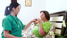 Senior woman taking medicine from nurse stock footage