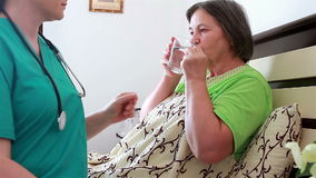 Senior woman taking medicine from nurse stock video footage