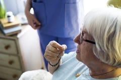 Senior woman taking a medicine Stock Photography