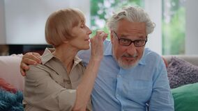 Free Senior Woman Taking Off Eyeglasses From Man. Mature Couple Sitting On Couch Stock Photo - 198845520