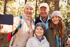 Senior woman taking outdoor selfie with grandkids and spouse Stock Photo