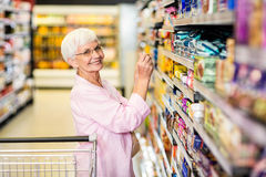 Senior woman taking a picture of product on shelf. In supermarket Royalty Free Stock Photography