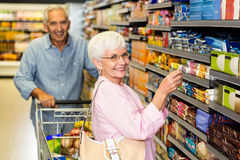 Senior woman taking a picture of product on shelf. Senior women taking a picture of product on shelf in supermarket Stock Photography