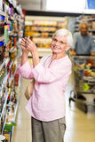 Senior woman taking a picture of product on shelf. Senior women taking a picture of product on shelf in supermarket Stock Photos