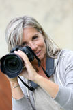 Senior woman taking pictures with a camera Royalty Free Stock Photos