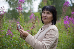 Senior woman taking pictures by phone in park Stock Photo