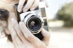 Senior woman taking pictures with vintage camera. Travel. Background Royalty Free Stock Photo