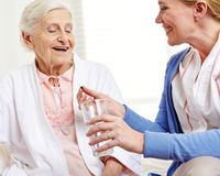 Senior woman taking pill with water Royalty Free Stock Images