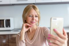 A senior woman taking a selfie at home stock images