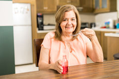 Senior woman taking some cough syrup Royalty Free Stock Image