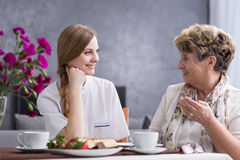 Senior woman talking with carer. Senior women talking with young carer, sitting beside table royalty free stock images