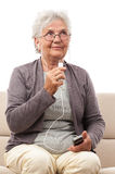 Senior woman talking at cellphone microphone looking up Stock Photography