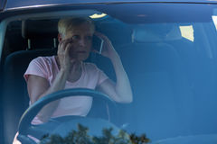 Senior woman talking on mobile phone in car Stock Photography