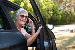 Senior woman talking on mobile phone in car Royalty Free Stock Photo