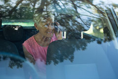 Senior woman talking on mobile phone in car Royalty Free Stock Photos