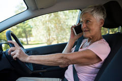 Senior woman talking on mobile phone in car Stock Photos