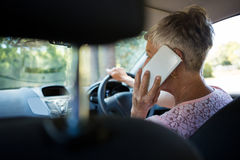 Senior woman talking on mobile phone while driving a car Stock Images