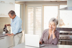 Senior woman talking on mobile phone with husband making tea in background Stock Photography