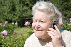 Senior woman talking on mobile phone outdoors Stock Photo