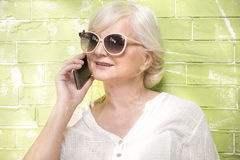 Senior woman talking by mobile phone. Royalty Free Stock Images