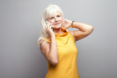 Senior woman talking by mobile phone in studio. Royalty Free Stock Photos