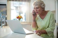 Senior woman talking on mobile phone while using laptop Stock Image