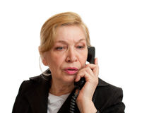 Senior Woman talking on the phone. In black suite on white background. Blond hair. Shot in studio Royalty Free Stock Image