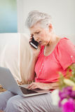 Senior woman talking on phone and using laptop Stock Photos