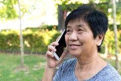 Senior woman talking on smart phone Stock Photo