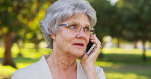 Senior woman talking on smartphone at the park Royalty Free Stock Images