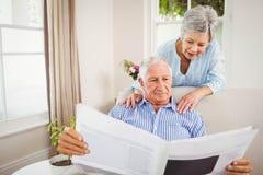 Senior woman talking to senior man reading newspaper Stock Images