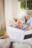 Senior woman talking to senior man reading newspaper Stock Photo