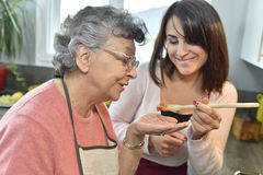 Senior woman tasting what home carer cookied Royalty Free Stock Photos