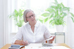 Senior woman tax declaration forms. Senior woman at home with a calculator and lots of bills and receipts, filling out the printed forms of the annual tax royalty free stock image