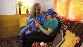 Senior woman teach granddaughter girl how to knit stock footage