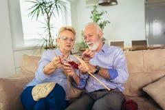 Senior woman teaching her husband the art of knitting woollen clothes stock photo
