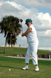 Senior woman tee off. A senior woman with a driver mid-swing during at the tee box on a tropical golf course Stock Photo