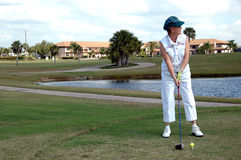 Senior woman tee off Royalty Free Stock Images