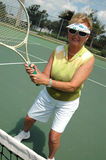 Senior woman on tennis court. An active senior woman on the tennis court royalty free stock photo