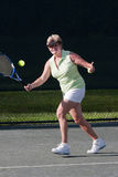 Senior woman tennis player about to hit a forehand shot Royalty Free Stock Photo